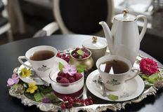 Chá em uns copos da porcelana, na sobremesa do panakota e na framboesa velhos em uma bandeja de prata velha retro foto de stock royalty free