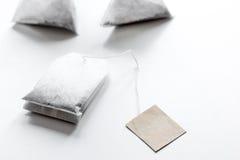 Chá em uns saquinhos de chá na zombaria branca da tabela acima Fotografia de Stock