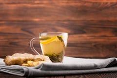 Chá erval Chá do limão doce e um gengibre do corte em um fundo de madeira Um copo do chá do gengibre Bebidas naturais e quentes p fotografia de stock royalty free
