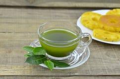 Chá fresco do matcha no copo com doce do abacaxi na tabela de madeira imagem de stock
