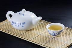 Chá japonês verde em uma esteira de bambu na pedra preta, em um copo branco do chá e em bule com opinião de chá verde de cima de imagem de stock royalty free