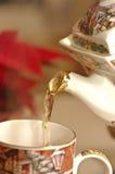 Chá morno de derramamento em um copo Imagem de Stock