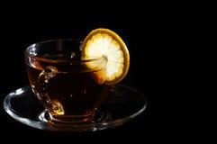 Chá no copo com o limão no fundo preto Fotografia de Stock