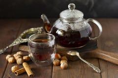 Chá no copo de vidro com bule próximo, vagem da baunilha e avelã no fundo de madeira, com colher e filtro próximo imagens de stock