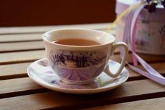 Chá no terraço, xícara de chá branca com teste padrão roxo Fotografia de Stock