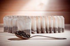 Chá nos sacos e chá fraco em uma colher em uma superfície de madeira foto de stock