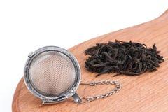 Chá preto, e filtro do chá com corrente, no fundo de madeira foto de stock royalty free