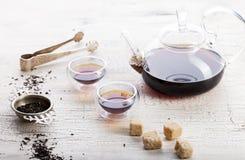 Chá preto em um bule transparente e em uns copos Fotos de Stock Royalty Free