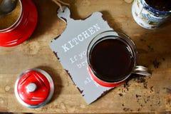 Chá preto em um vidro em um suporte de vidro vermelho foto de stock