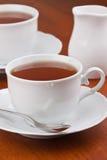 Chá preto em umas canecas com saucers Fotos de Stock