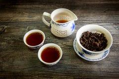 Chá preto em uns copos e em um bule do chinês tradicional na tabela de madeira Fotos de Stock Royalty Free
