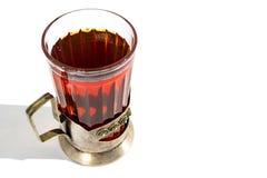 Ch? preto quente forte em um copo de vidro em um suporte de copo do metal em um fundo branco com uma sombra imagens de stock