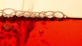 Chá preto vermelho que derrama no fim de vidro do bule acima filme