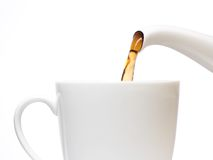 Chá que derrama no copo Fotografia de Stock