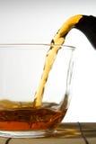 Chá que derrama no copo de vidro Fotos de Stock Royalty Free