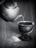 Chá que está sendo derramado em um copo cerâmico de um bule Imagens de Stock