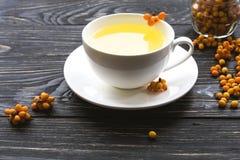 Chá quente com as bagas de espinheiro cerval frescas do mar Fotografia de Stock Royalty Free