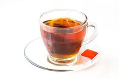 Chá quente com o saquinho de chá no copo e em uns pires transparentes Fotos de Stock
