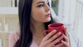 Chá quente da bebida moreno da menina das canecas vermelhas video estoque