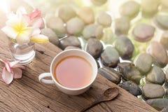 Chá quente no copo branco com as flores na água de madeira b da pedra do seixo Fotografia de Stock Royalty Free