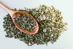 Chá seco verde e colher de madeira fotografia de stock royalty free