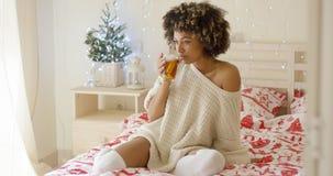 Chá sorvendo da jovem mulher quando assentado na cama fotografia de stock