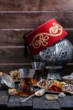 Chá turco com os copos de vidro autênticos Dois copos do chá turco e doces no fundo de madeira escuro Foto de Stock