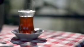 Chá turco em uma toalha de mesa quadriculado do teste padrão filme