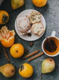 Chá, varas de canela, queques, peras, anis de estrela e caquis Fotografia de Stock