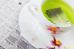 Chá verde com jornal imagens de stock royalty free