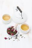 Chá verde com rosebuds, copos e bule na tabela de madeira branca Fotografia de Stock