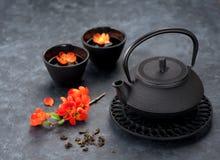 Chá verde e flores Bule e copos asiáticos do estilo do ferro preto Foto de Stock Royalty Free