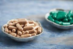 Chá verde e L - cápsulas da carnitina Conceito para um suplemento dietético saudável imagens de stock