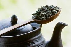 Chá verde em uma colher de madeira no bule Fotografia de Stock Royalty Free