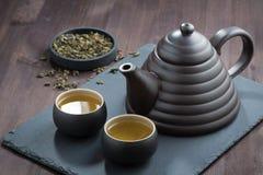 Chá verde recentemente fabricado cerveja em mercadorias cerâmicos na tabela de madeira Fotografia de Stock