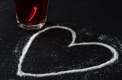 Chá vermelho das bagas no vidro e no açúcar derramado na forma do coração Imagem de Stock Royalty Free