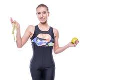 Chándal delgado y sano de la ropa de deportes de la mujer que lleva joven que sostiene la cinta de la medida y la manzana verde a foto de archivo libre de regalías