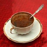 Chávena de café com a colher em um fundo vermelho imagens de stock royalty free