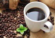 Chávena de café com feijões e folha fotografia de stock