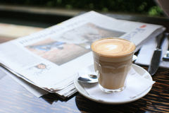 Chávena de café com papel da notícia na tabela Fotografia de Stock