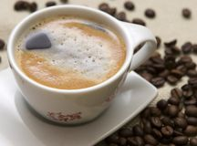Chávena de café e grões sobre o sackcloth fotos de stock royalty free
