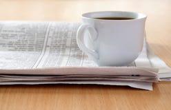 Chávena de café e o jornal foto de stock