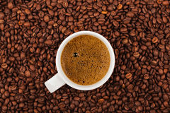 Chávena de café em feijões de café Fotos de Stock Royalty Free