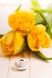 Chávena de café minúscula e tulipas amarelas Fotos de Stock