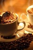 Chávenas de café, cheias dos feijões. Imagem de Stock