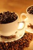 Chávenas de café, cheias dos feijões. Fotos de Stock