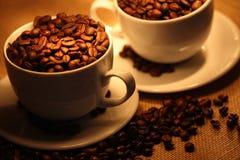 Chávenas de café, cheias dos feijões. Foto de Stock Royalty Free