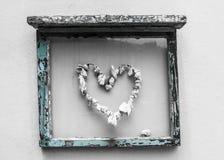Châssis de fenêtre bleu avec un coeur fait de coquilles Photographie stock libre de droits