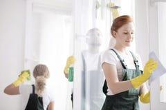 Châssis de fenêtre de nettoyage de femme Photographie stock libre de droits