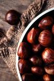 Châtaignes fraîches sur le sac brun de sac Grands écrous savoureux mûrs de coffre dessus Photographie stock libre de droits